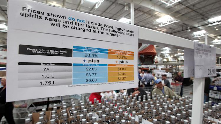 A sign explains the taxes that will be added for liquor customers at check-out at a Costco warehouse store Friday, June 1, 2012, in Seattle. Private retailers begin selling spirits for the first time under a voter-approved initiative kicking the state out of the liquor business. The initiative allows stores larger than 10,000 square feet and some smaller stores to sell hard alcohol.(AP Photo/Elaine Thompson)