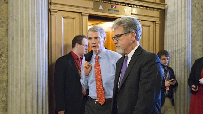 Sen. Tom Coburn, R-Okla., right, and Sen. Rob Portman, R-Ohio, left, arrive for the vote to end debate on the nomination of former GOP senator Chuck Hagel as the nation's next secretary of defense, at the Capitol in Washington, Thursday, Feb. 14, 2013. (AP Photo/J. Scott Applewhite)