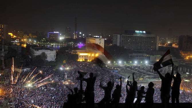 """FILE - In this Wednesday, July 3, 2013 file photo, Egyptians wave national flags as fireworks light the sky over Tahrir Square, where hundreds thousands opponents of Egypt's Islamist President Mohammed Morsi celebrate his ouster in Cairo, Egypt. Almost a quarter-century ago, a young American political scientist achieved global academic celebrity by proclaiming that the collapse of communism had ended the discussion on how to run societies, leaving """"Western liberal democracy as the final form of human government."""" In Egypt and around the Middle East, after a summer of violence and upheaval, the discussion, however, is still going strong. And almost three years into the Arab Spring revolts, profound uncertainties remain. (AP Photo/Amr Nabil, File)"""