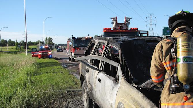 """This Sunday, June 29, 2014 image provided by the Minnesota State Patrol shows a fireman in front of the burnt wreckage of a sports utility vehicle along Interstate 35W in New Brighton, Minn. A Good Samaritan showed """"superhuman strength"""" when he bent the door of the burning sport utility vehicle and rescued another motorist, a state trooper said. (AP Photo/Minnesota State Patrol)"""