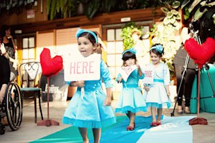 Flower girls carrying sign.