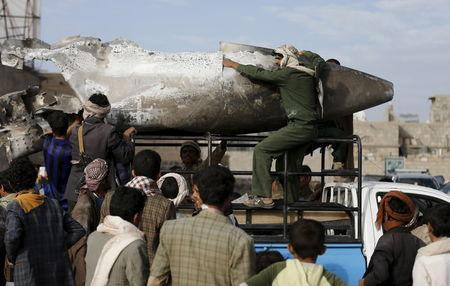 Houthi rebels transport part of a Saudi fighter jet found in Bani Harith district north of Yemen's capital Sanaa
