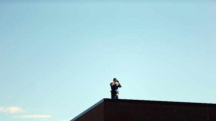 A police officer is seen on the rooftop at the Arapahoe County Courthouse July 30, 2012 in Centennial, Colorado