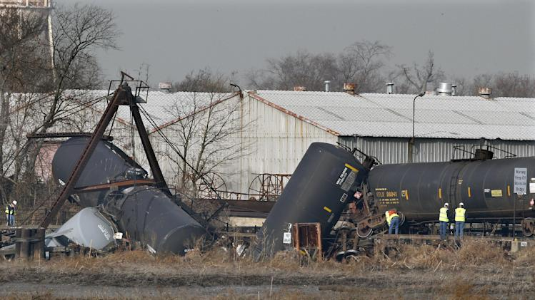 Officials work the scene of derailed freight train tank cars in Paulsboro, N.J., Friday, Nov. 30, 2012. People in three southern New Jersey towns were told Friday to stay inside after a freight train derailed and several tanker cars carrying hazardous materials toppled from a bridge and into a creek. At least one tanker car may contain vinyl chloride, Gloucester County Emergency Management director J. Thomas Butts told WPVI-TV. (AP Photo/Mel Evans)