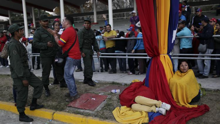 Security officers block a man trying to cut the line of people waiting to see the body of Venezuela's late President Hugo Chavez outside the military academy where he is lying in state in Caracas, Venezuela on Saturday, March 9, 2013. Chavez died on March 5, 2013 after a nearly two-year bout with cancer. He was 58. (AP Photo/Rodrigo Abd)