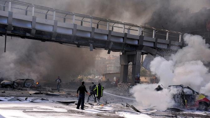 This photo released by the Syrian official news agency SANA, shows Syrian fire fighters extinguishing burning cars after huge explosion that shook central Damascus, Syria, Thursday, Feb. 21, 2013. A car bomb shook central Damascus on Thursday, exploding near the headquarters of the ruling Baath party and the Russian Embassy, eyewitnesses and opposition activists said. (AP Photo/SANA)