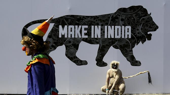 A performer walks past another at the exhibition centre of the 'Make In India' week in Mumbai