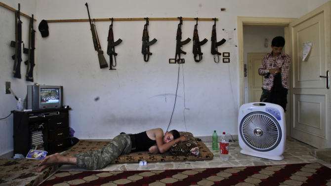 A Syrian rebel, sleeps after returning back from fighting against Syrian army forces in Aleppo, at a rebel headquarters in Marea on the outskirts of Aleppo city, Syria, Sunday, Aug. 26, 2012. (AP Photo/Muhammed Muheisen)