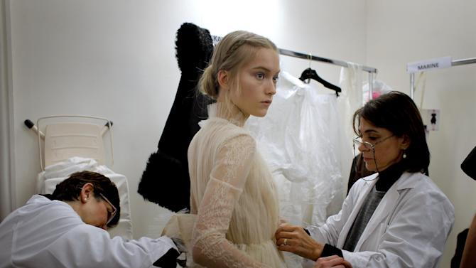 A model  is dressed up backstage prior to the Valentino Spring Summer 2013 Haute Couture fashion collection, presented in Paris, Wednesday, Jan.23, 2013. (AP Photo/Christophe Ena)