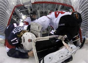 Team USA's Lamoureux crashes into Switzerland's goalie Schelling as Switzerland's Benz defends during the third period of their women's preliminary round hockey game at the Sochi 2014 Winter Olympic Games