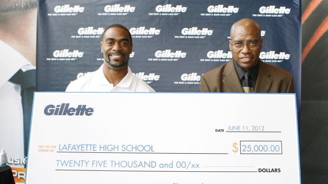 COMMERCIAL IMAGE - American 100m record holder Tyson Gay, left, present his former high school coach Ken Northington with a $25,000 Great Start grant to support the next generation of men at Gillette World Shaving at Headquarters, Monday,  June 11, 2012, in Boston. The grant will support the track and field team at Lafayette High School in Lexington, KY., where Gay got his great start. (Photo by Bizuayehu Tesfaye/Invision for Gillette/AP Images)