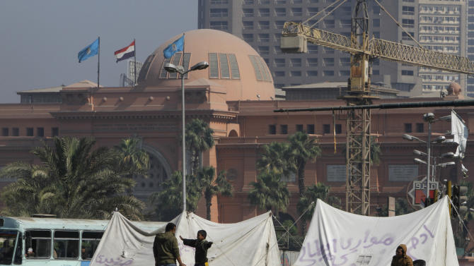 Egyptians chat outside their tents in front of the Egyptian museum in Tahrir Square, in Cairo, Egypt, Saturday, April 27, 2013. Egypt's economy, particularly the vital tourism sector, has been hit hard by the instability that has followed the 2011 uprising that forced longtime autocratic ruler Hosni Mubarak from power. (AP Photo/  Amr Nabil)