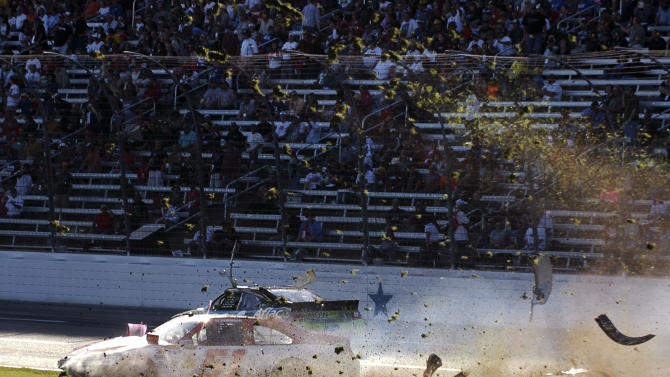 Debris flies as AJ Allmendinger (51) slides through the infield after colliding with Carl Edwards, rear, during the NASCAR Sprint Cup Series auto race at Texas Motor Speedway, Sunday, Nov. 4, 2012, in Fort Worth, Texas. (AP Photo/Randy Holt )
