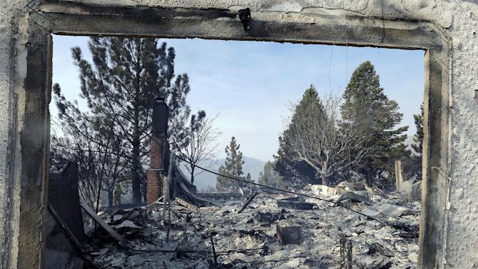 A window frames the view of a home damaged by wildfires in Lake Hughes, Calif., early Sunday, June 2, 2013. Erratic wind fanned a blaze in the Angeles National Forest to nearly 41 square miles early Sunday, after fast-moving flames triggered the evacuation of nearly 1,000 homes in Lake Hughes and Lake Elizabeth, officials said. (AP Photo/Reed Saxon)