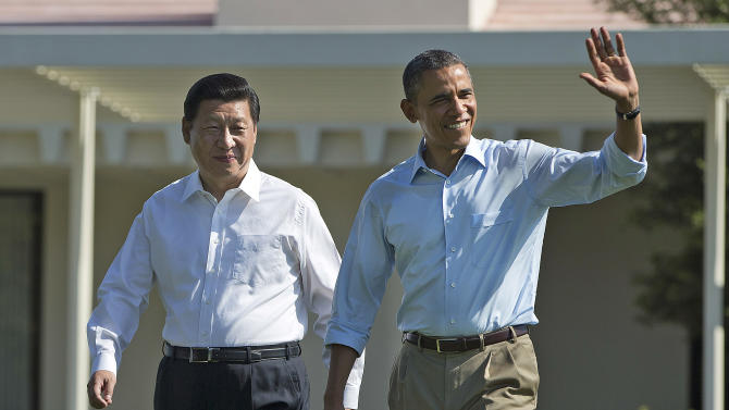 """President Barack Obama, right, walks with Chinese President Xi Jinping at the Annenberg Retreat of the Sunnylands estate Saturday, June 8, 2013, in Rancho Mirage, Calif. During their walk President Obama told reporters his meetings with President Xi have been """"terrific."""" The issue of cyber espionage hangs over the summit, although both leaders carefully avoided accusing each other of the practice. (AP Photo/Evan Vucci)"""