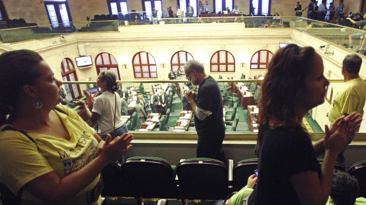 Schoolteachers protest inside the chamber of the Lower House of Congress in San Juan