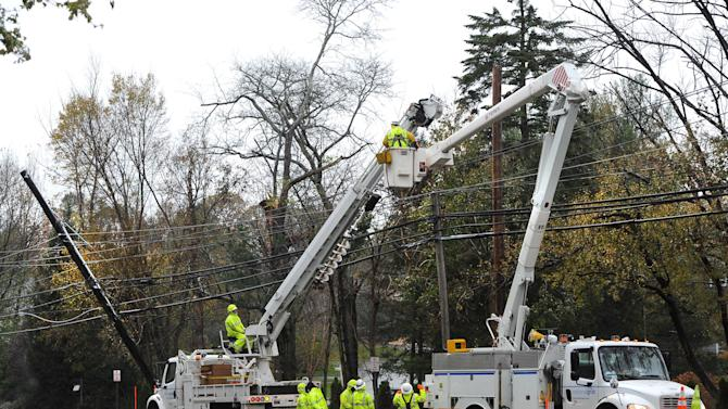 FILE- In this Nov. 7, 2012 file photo, a National Grid crew from Fredonia, N.Y. repair power lines in Port Washington, N.Y., that were damaged during Superstorm Sandy. Thousands of utility workers from New York, Rhode Island and Massachusetts say many are still waiting to be fully compensated for their efforts to restore power after Superstorm Sandy. (AP Photo/Kathy Kmonicek, File)
