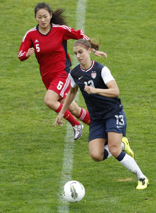 Alex Morgan of the U.S. and China's Wu Haiyan run towards ball during  Algarve Cup soccer match in Albufeira