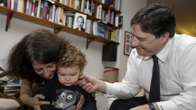 """In this Jan. 30, 2013 photo, Drew and Frances Pardus-Abbadessa play with their son Pavol, 1, at their apartment in New York, where they hope another son, from Kyrgyzstan, will one day  join them.  The Pardus-Abbadessa family were among a group initially known as the """"Kyrgyz 65"""" - Americans who were in the process of adopting 65 orphans from the Central Asian republic when it suspended international adoptions in 2008 due to allegations of fraud. Some of the children were placed in domestic adoptions, and last summer nine of the remaining children finally were allowed to go to America. The Pardus-Abbadessas are now among 16 U.S. families still waiting, five years later. (AP Photo/Seth Wenig)"""