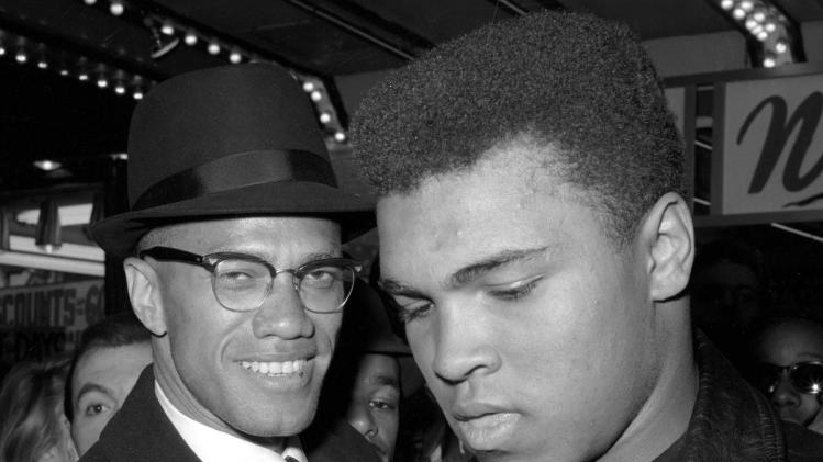 FILE - In this March 1, 1964, file photo, heavyweight boxing champion Muhammad Ali, right, is shown with black muslim leader Malcolm X outside the Trans-Lux Newsreel Theater in New York, after viewing the screening of a film about Ali's title fight with Sonny Liston. Ali turns 70 on Jan. 17, 2012.  (AP Photo/File)
