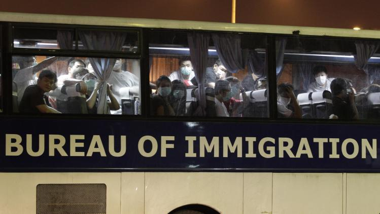 Taiwanese, suspected of being members of a fraud syndicate, sit inside a Philippine Bureau of Immigration bus as they arrive at Manila's International Airport, Philippines early Wednesday Sept. 19, 2012. About 279 Taiwanese were deported following their arrest for alleged online fraud. One died while others began falling ill in crowded makeshift detention facilities, officials said. (AP Photo/Aaron Favila)
