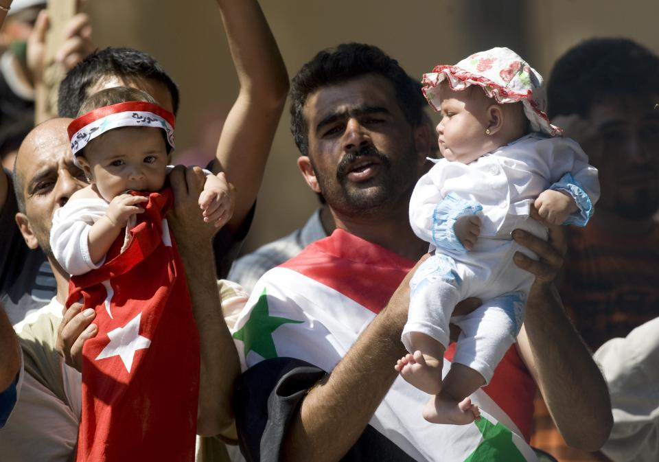 Two men hold up their babies, as Syrian refugees demonstrate against their country's regime and its leader Bashar al-Assad in a camp in the Turkish border town of Yayladagi in Hatay province, Turkey, Wednesday, June 29, 2011.(AP Photo/Burhan Ozbilici)
