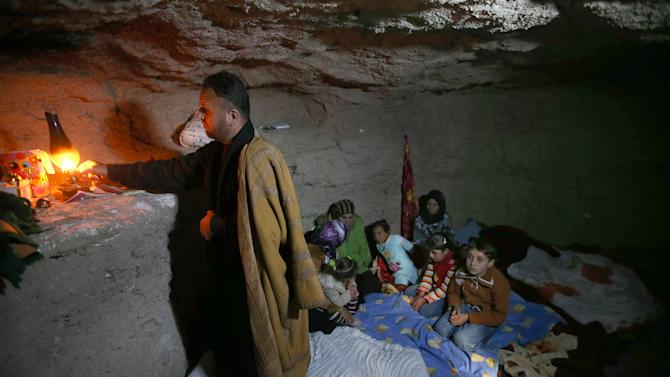 FILE - A defected Syrian policeman, Adnan al-Hamod, 33, lights a kerosene lamp at an underground cave used for shelter from Syrian government forces shelling and airstrikes, at Jirjanaz village, in Idlib province, Syria, Thursday Feb. 28, 2013. (AP Photo/Hussein Malla, File)