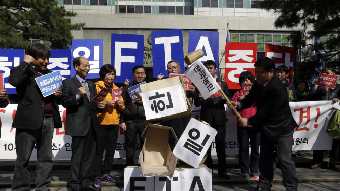 "South Korean farmers smash boxes symbolizing the Free Trade Agreement between South Korea, Japan, and China during a rally denouncing the FTA talks in front of the venue where the discussions are being held, in Seoul, South Korea, Tuesday, March 26, 2013.  Negotiations for a Free Trade Agreement between the three countries will be held from March 26 - 28. The writing reads ""Stop, FTA between South Korea, China and Japan."" (AP Photo/Lee Jin-man)"