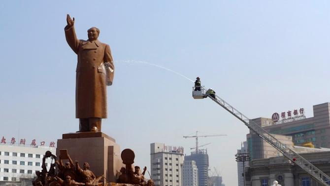 A firefighter uses a water cannon to clean a statue of late Chinese Chairman Mao Zedong in Shenyang