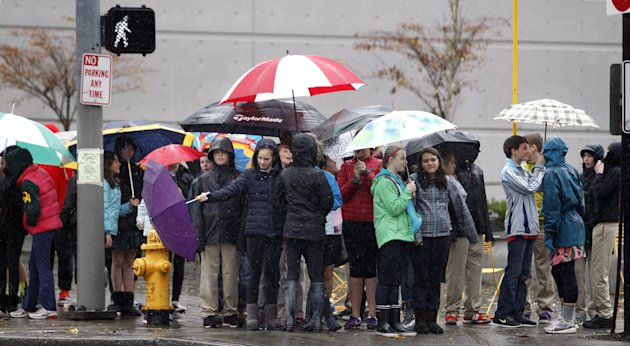 School children huddle under umbrellas as they wait to cross a street during an outing Monday, Nov. 19, 2012, in Seattle. Wet and windy weather with mountain snow will continue this week in Washington