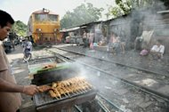 A man cooks barbecue chicken as a train passes by shack houses in Bangkok. Thailand's cabinet has approved a plan to spend $68 bn on a high-speed railway and other transportation mega projects to drive the nation's economic development
