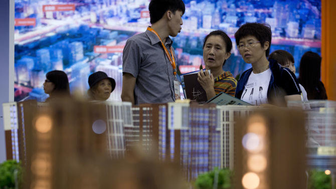 FILE -In this Sept. 21, 201 file photo, people view housing models on display during the China Property and Investment Show in Beijing, China. People in China are increasingly worried about corruption, inequality and food safety, according to a survey that also found that about half of Chinese like American ideas about democracy.  (AP Photo/Andy Wong, File)