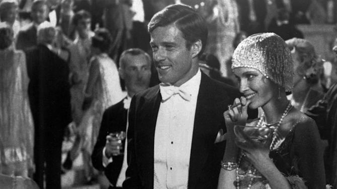 """FILE - This 1974 file photo originally released by Paramount Pictures shows Robert Redford as Jay Gatsby, and Mia Farrow as Daisy, in """"The Great Gatsby.""""  F. Scott Fitzgerald's """"The Great Gatsby"""" is short, almost novella size. It features larger-than-life characters, glamorous extravagance and dramatic deaths. On its surface, it's almost certainly the most Hollywood-friendly of the great American novels. But the poetry of """"Gatsby"""" has remained largely locked on the page. Since it was published in 1925, it has been staged as a play and a musical, spawned four previous film adaptations and even been made into an 8-bit Nintendo-style video game in with Nick Carraway must evade cocktail-dispensing butlers and flappers while trying to find Gatsby. On May 10, 2013, Baz Luhrmann will release his """"Gatsby,"""" a 3-D blockbuster spectacle with a star-studded cast, a contemporary soundtrack and hopes of cracking the code of Fitzgerald's mysterious novel. (AP Photo/ Paramount Pictures, File)"""