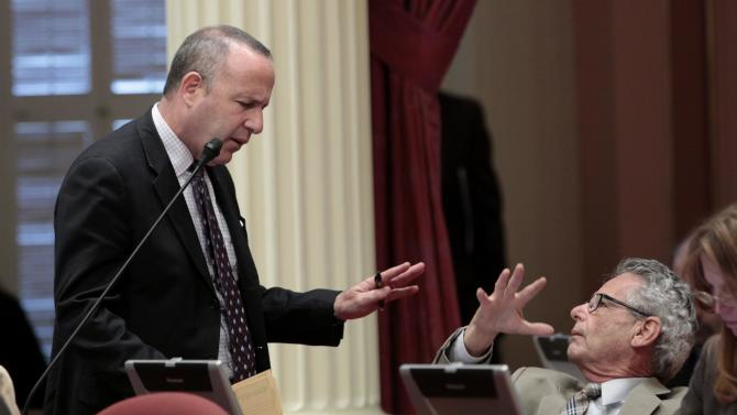 State Senate President Pro Tem Darrell Steinberg, D-Sacramento, left, tries to convince Sen. Alan Lowenthal, D-Long Beach, to vote for a bill to authorize  about $4.5 billion in funding for a high-speed rail system, at the Capitol in Sacramento, Calif., Friday, July 6, 2012.   The bill, which would allow the state to begin selling $2.6 billion in voter -approved bonds, was approved by a 21-16 vote and now goes to Gov. Jerry Brown who has supports the measure.   Lowenthal was among the three Democrats in the Senate to oppose the bill.(AP Photo/Rich Pedroncelli)