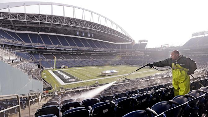 A worker, who declined to be identified, cleans seats at CenturyLink Field in preparation for the NFL football NFC championship in Seattle, Wednesday, Jan. 15, 2014. The Seattle Seahawks play the San Francisco 49ers on Sunday. (AP Photo/Elaine Thompson)