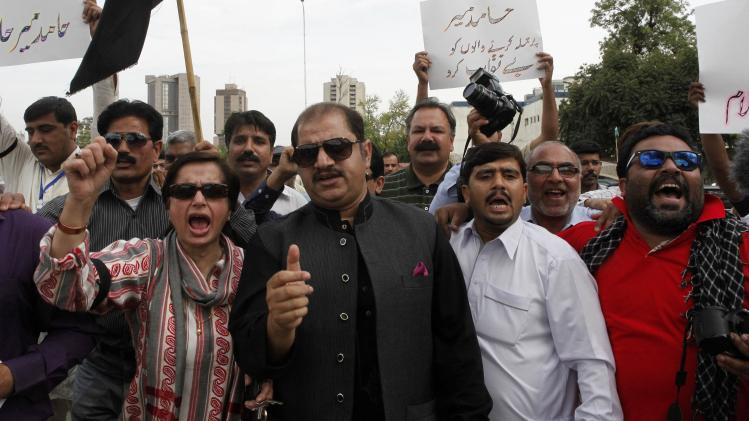 Pakistani journalists chant slogans during a protest, called by PFUJ, against the attack on television anchorperson Hamid Mir, outside the press club in Islamabad