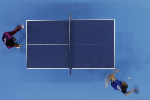 Djibouti's Farah Yasmin Hassan, left, plays Brazil's Caroline Kumahara during preliminary round table tennis match at the 2012 Summer Olympics, Saturday, July 28, 2012, in London. (AP Photo/Sergei Grits)