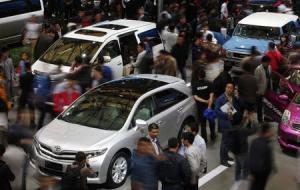File photo shows people looking at Toyota cars during the Shanghai International Automobile Industry Exhibition