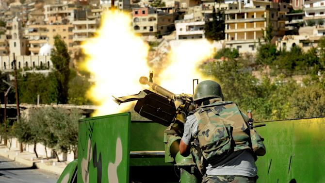 In this Saturday, Sept. 7, 2013 photo released by the Syrian official news agency SANA, a Syrian military solider fires a heavy machine gun during clashes with rebels in Maaloula village, northeast of the capital Damascus, Syria. Rebels including al-Qaida-linked fighters gained control of Maaloula, Syrian activists said Sunday. Government media provided a dramatically different account of the battle suggesting regime forces were winning. It was impossible to independently verify the reports from Maaloula, a scenic mountain community known for being one of the few places in the world where residents still speak the ancient Middle Eastern language of Aramaic. (AP Photo/SANA)