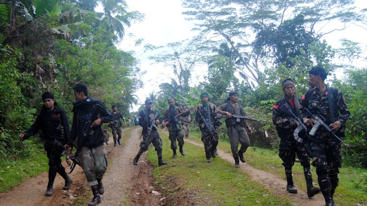 In this Feb. 7, 2013 photo, Moro National Liberation Front (MNLF) rebels, who signed a peace agreement with the Philippine government in 1996, patrol a remote village on the volatile island of Jolo, Sulu province in southern Philippines. After years of fighting the government from hidden jungle bases in the southern Philippines, an Al-Qaida-linked militant group is facing a new adversary: fellow Muslim insurgents who can match their guerrilla battle tactics and are eager to regain their lost stature by fighting the widely-condemned terrorist group. The emerging enmity between the Abu Sayyaf militants and the Moro rebels could bolster a decade-long campaign by the Philippines and Western countries to isolate the al-Qaida offshoot Abu Sayyaf, which remains one of the most dangerous groups in Southeast Asia. (AP Photo/Nickee Butlangan)