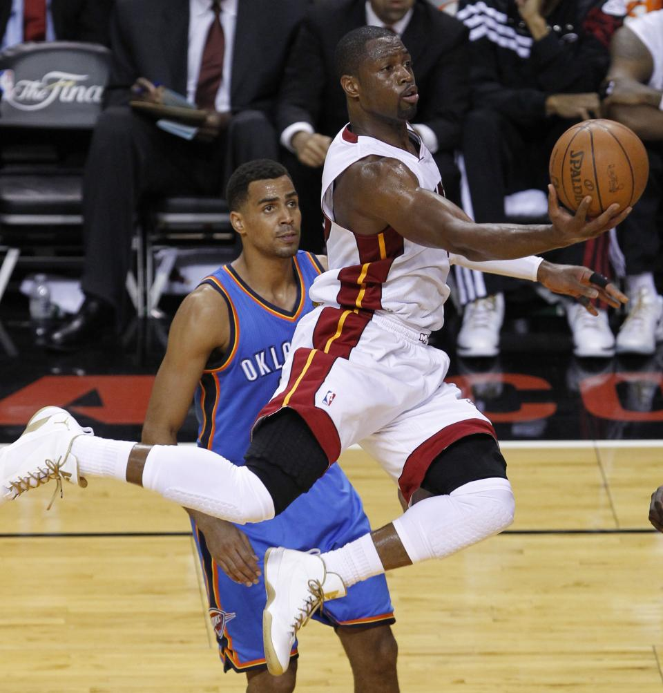 Miami Heat shooting guard Dwyane Wade (3) gets past Oklahoma City Thunder shooting guard Thabo Sefolosha (2) of Switzerland to shoot the ball during the first half at Game 3 of the NBA Finals basketball series, Sunday, June 17, 2012, in Miami. (AP Photo/Wilfredo Lee)
