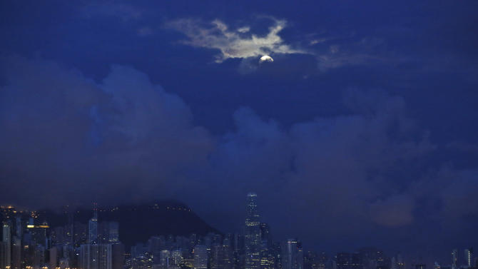 "In this Aug. 11, 2014 photo, a perigee moon, also known as a super moon is half covered by cloud during the ""Hungry Ghost Festival"" in Hong Kong. Countless hungry and restless ghosts are roaming Hong Kong, and the world, to visit their living ancestors, at least according to Chinese convention. In traditional Chinese belief, the seventh month of the lunar year is reserved for the Hungry Ghost festival, or Yu Lan, a raucous celebration marked by feasts and music. This year the festival began Aug. 10. According to folklore, the ghosts who wander the physical world are ravenous and envious after dying without descendants or because they were not venerated by relatives who are still alive. (AP Photo/Kin Cheung)"
