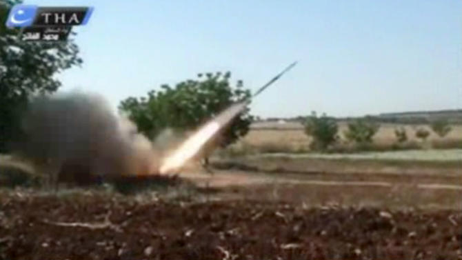 This image from amateur video obtained by a group which calls itself Ugarit News, which is consistent with AP reporting, shows a rocket fired by Syrian rebels in Qusair, Syria, Tuesday, May 28, 2013. Europe's decision to allow member states to arm Syrian rebels and Russia's renewed pledge to send advanced missiles to the Syria regime could spur an arms race in an already brutal civil war and increasingly turn it into a East-West proxy fight. Britain promises not to transfer any arms before diplomacy is given a chance in Syria peace talks expected next month, while a top rebel commander says he needs Western anti-aircraft and anti-tank missiles now to prevent more regime gains on the battlefield. (AP Photo/Ugarit News via AP video)