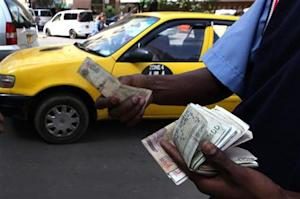 A fuel attendant handles Kenyan shilling notes at a petrol station in the capital Nairobi