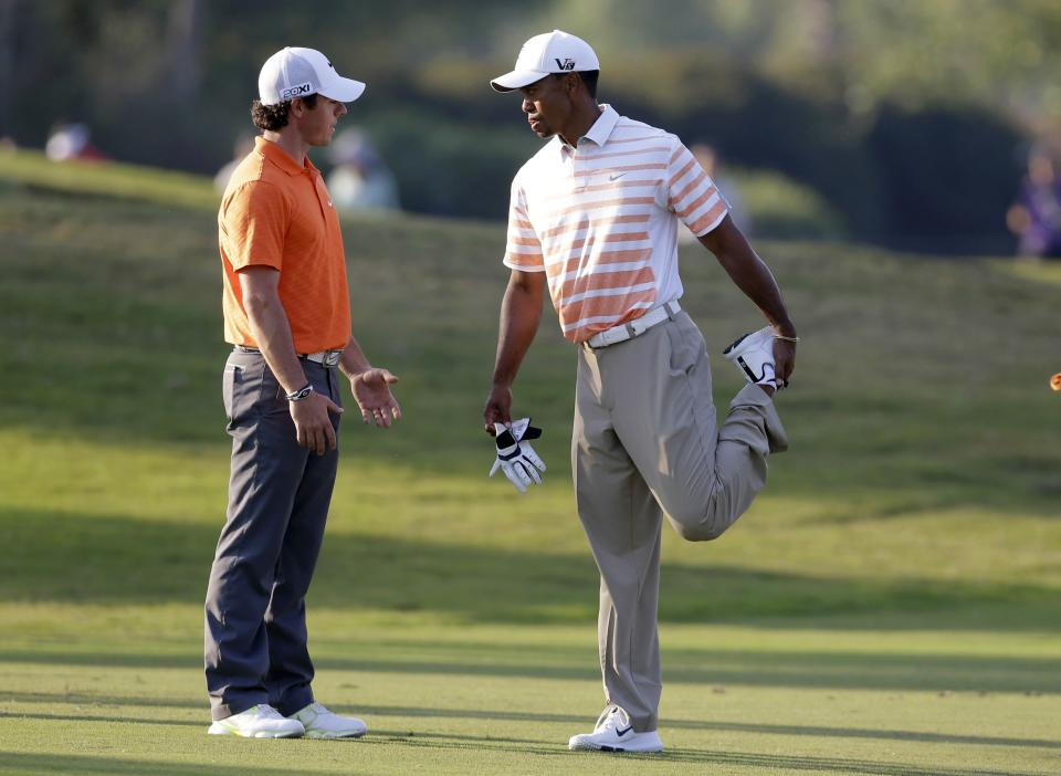 Tiger Woods, right, stretches as he and Rory McIlroy, of Northern Ireland, talk while waiting to hit on the 17th fairway during the second round of the Cadillac Championship golf tournament on Friday, March 8, 2013 in Doral, Fla. (AP Photo/Wilfredo Lee)