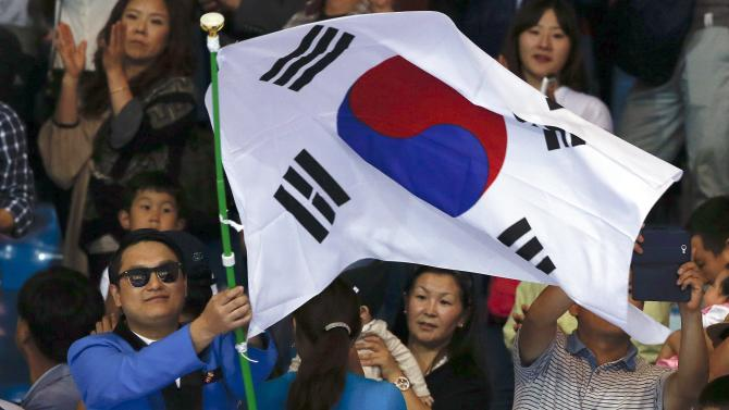 A fan waves a South Korean flag during the judo event at Dowon Gymnasium during the 17th Asian Games in Incheon