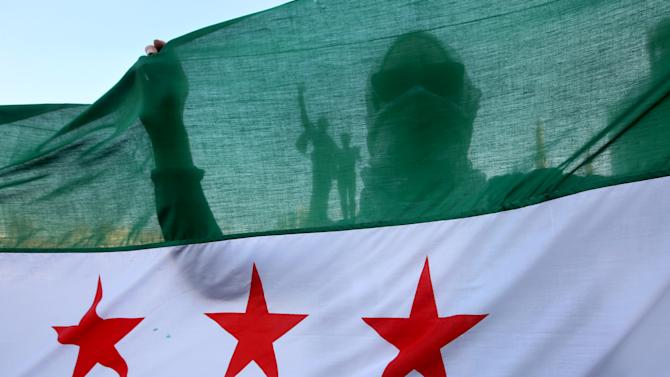 A Syrian activist is silhouetted through the Syrian revolution flag during a protest against the participation of Hezbollah members in the fighting in the Syrian town of Qusair, at the Martyrs square in Beirut, Lebanon, Tuesday May 21, 2013. Backed by elite troops of Lebanon's militant Hezbollah group, Syrian government forces fought rebels in a strategic opposition-held Syrian town near the Lebanese border for the third straight day Tuesday. Lebanese security officials said fighting between Syrian troops and rebels over the town of Qusair had spread to the village of Hit, on the Syrian side near the border with Lebanon.(AP Photo/Hussein Malla)