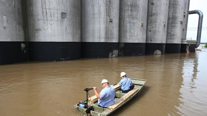 Workers from the ConAgra Mill in Alton, Ill., boat down West Broadway to work on Tuesday, June 4, 2013. West Broadway, also known as the Great River Road, is closed because of floodwaters from the Mississippi River. (AP Photo/The Telegraph, John Badman)  THE NEWS-DEMOCRAT AND THE POST-DISPATCH OUT
