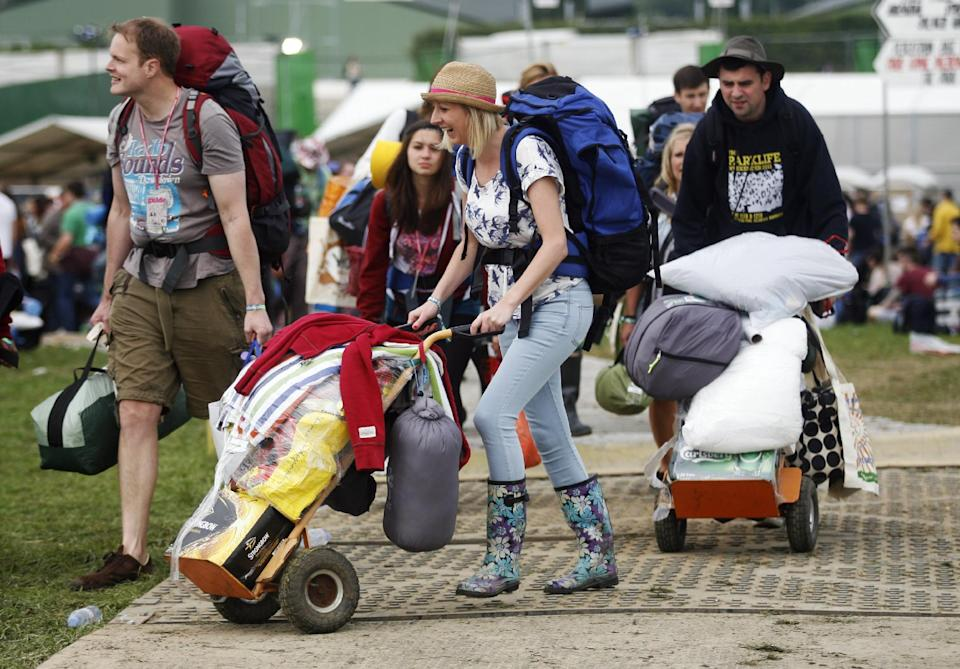 Festival goers arrive at the Glastonbury Music Festival site at Glastonbury England on Wednesday, June 26, 2013. Thousands are to arrive for the three day festival that starts on Friday, June 28 2013 with headliners, Arctic Monkeys, the Rolling Stones and Mumford and Sons. (Photo by Jim Ross/Invision/AP)