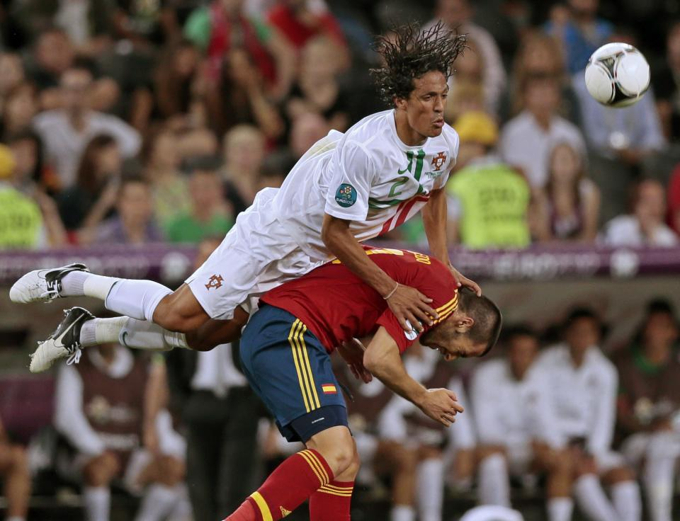 Portugal's Bruno Alves, top, falls over Spain's Alvaro Negredo during the Euro 2012 soccer championship semifinal match between Spain and Portugal in Donetsk, Ukraine, Wednesday, June 27, 2012. (AP Photo/Ivan Sekretarev)